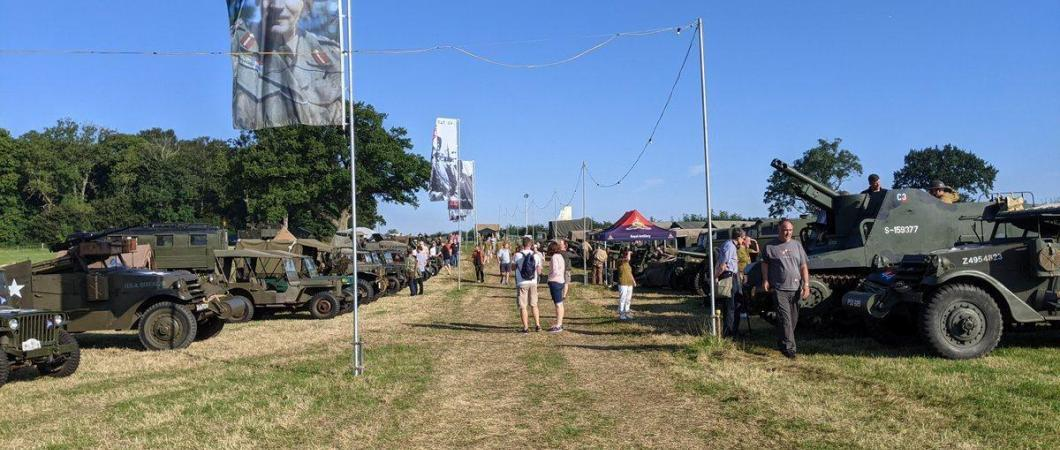 A grassy avenue at We Have Ways Fest with military vehicles displayed on both sides
