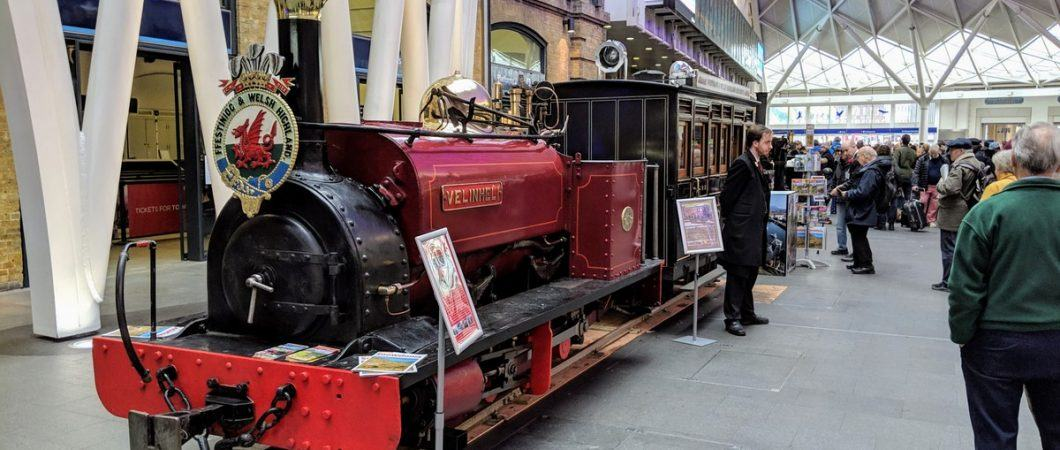 A small maroon coloured steam engine on temporary tracks in the passenger concourse