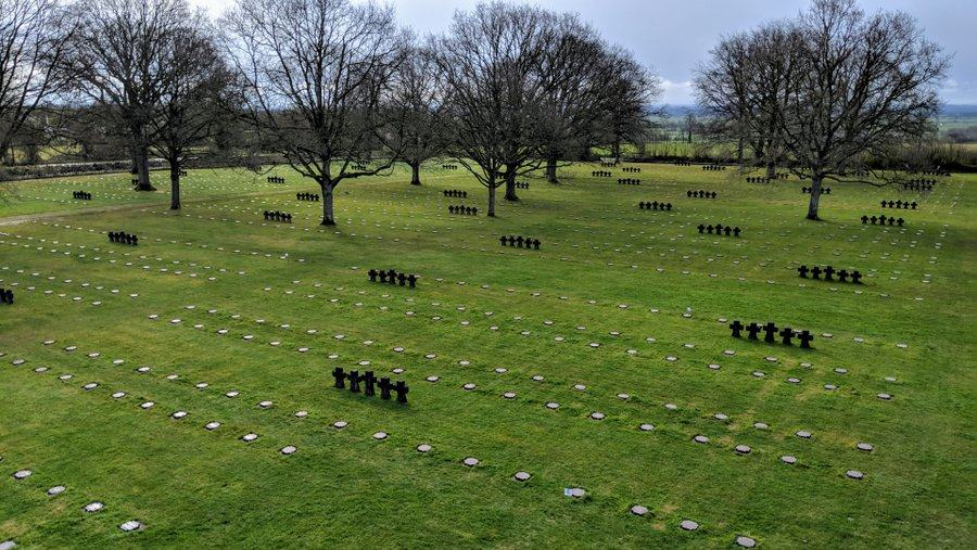 Multiple rows of marker stones and groups of crosses on the green grass