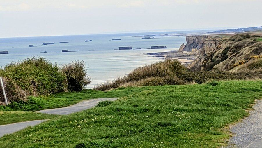 View past cliffs along the coast with remains of the Mulberry harbour caissons out to sea