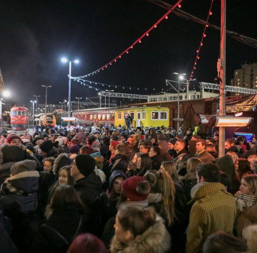 Music gig audience dress warmly with historic locomotives behind
