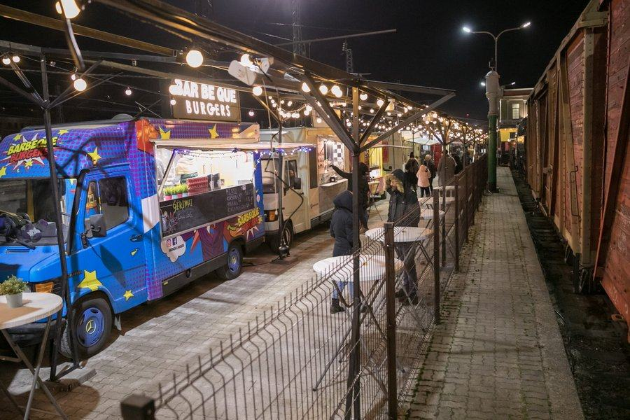 A row of food trucks face a row of historic rail vans