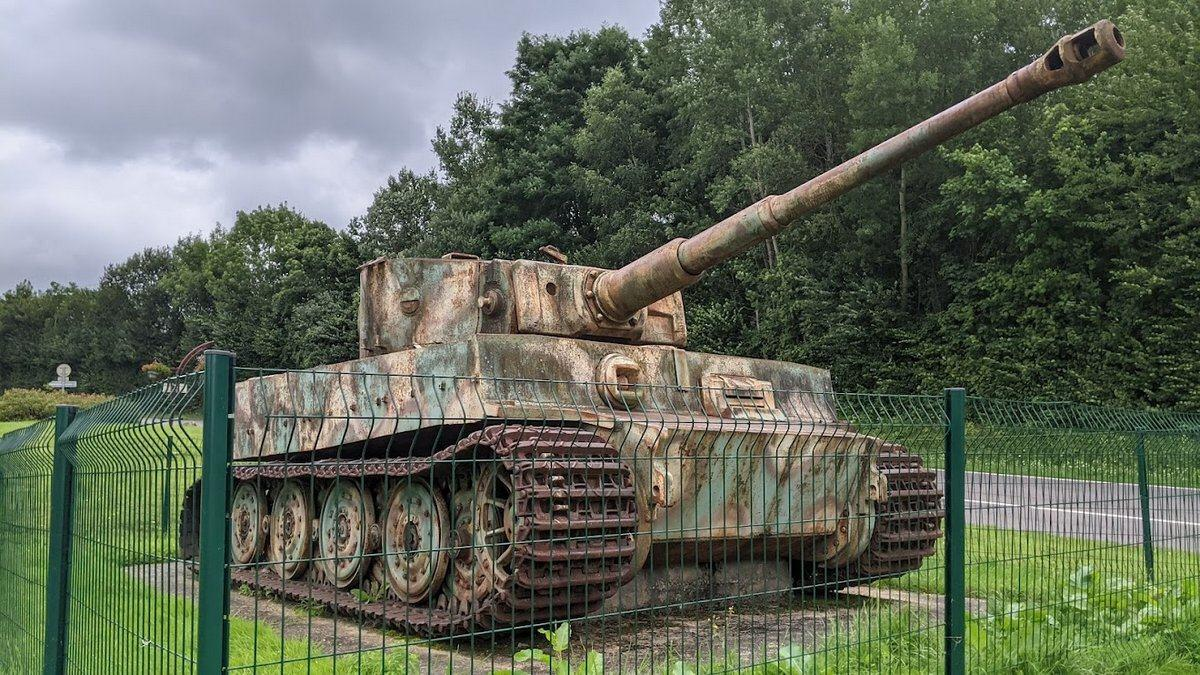 Tiger tank in faded camouflage behind its protective green fence