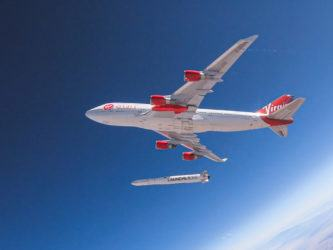 A red and white painted Virgin jumbo jet high in the blue atmosphere... drops a rocket from under its wing!