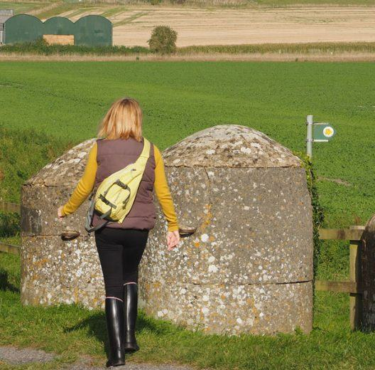 Woman walks toward WW2 anti-tank obstacles in Wiltshire field