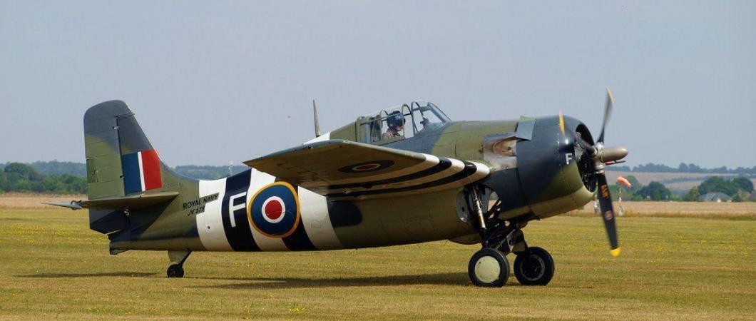 A stubby single-engine fighterwith green & brown camouflage and B/W Invasion Striped, taxies on the grass