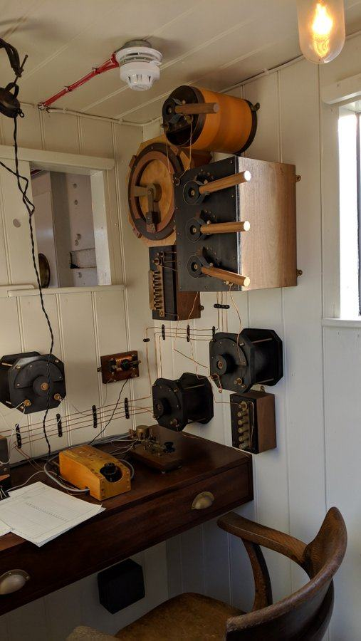 Small cabin with a morse key on a table and electrical gear on the wall