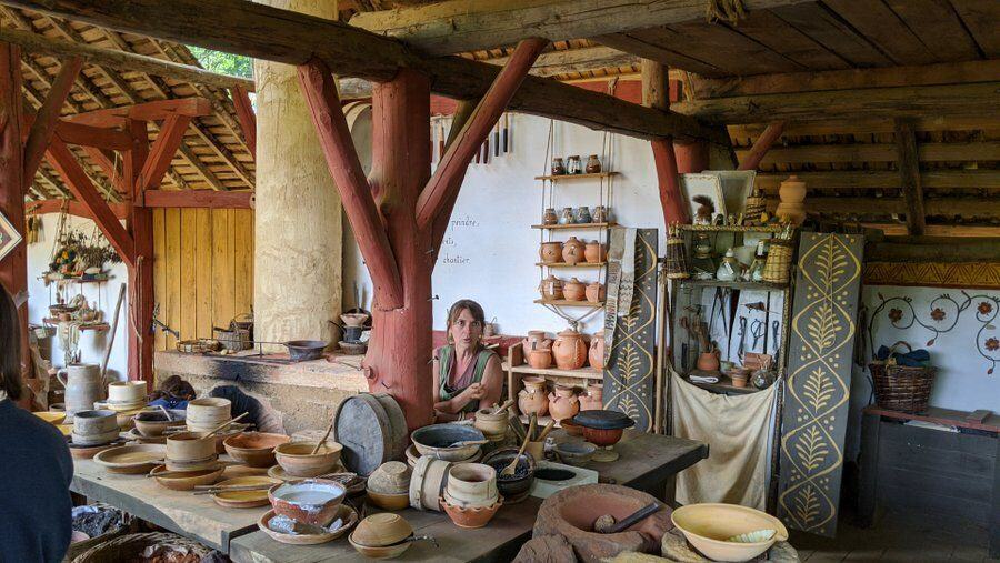 A woman surrounded by small pots with pigments