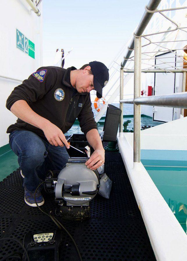 Man working with a screwdriver on a small remote underwater vehicle