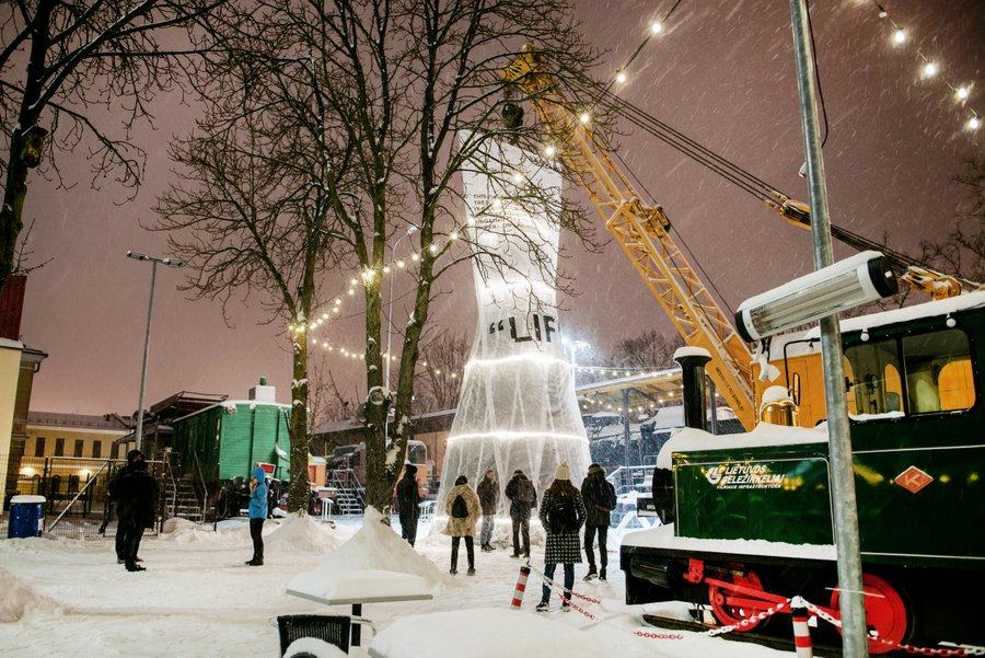 In a snow flurry at night the giant Christmas tree is an illuminated translucent white plastic bag is dangling from a crane next to a green steam loco
