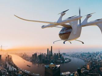 Artist's rendition: A futuristic white helicopter shaped aircraft descends towards a modern city at dusk
