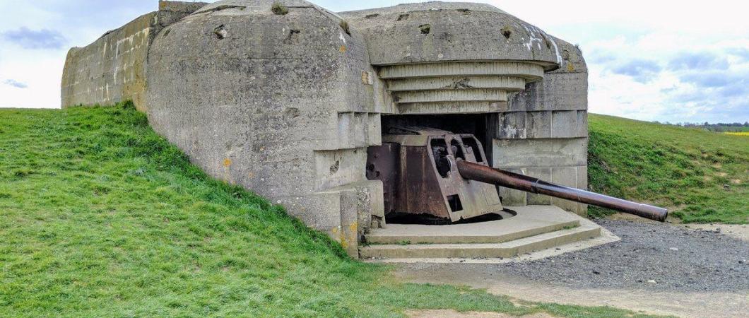 A grey concrete gun emplacement sunk into a grassy embankment