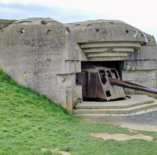 A grey concrete gun emplacement sunk into a grassy embankment