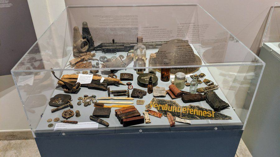 A display case with rusty helmets and other battlefield debris