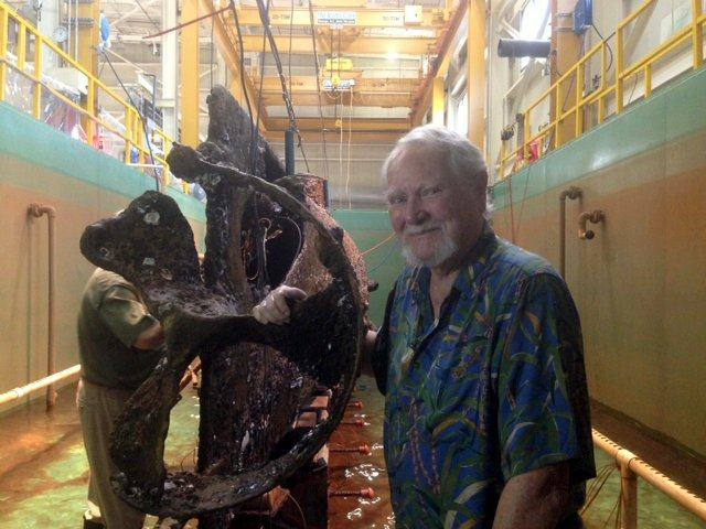 Author Clive Cussler stand with his hand on the propeller of the Hunley