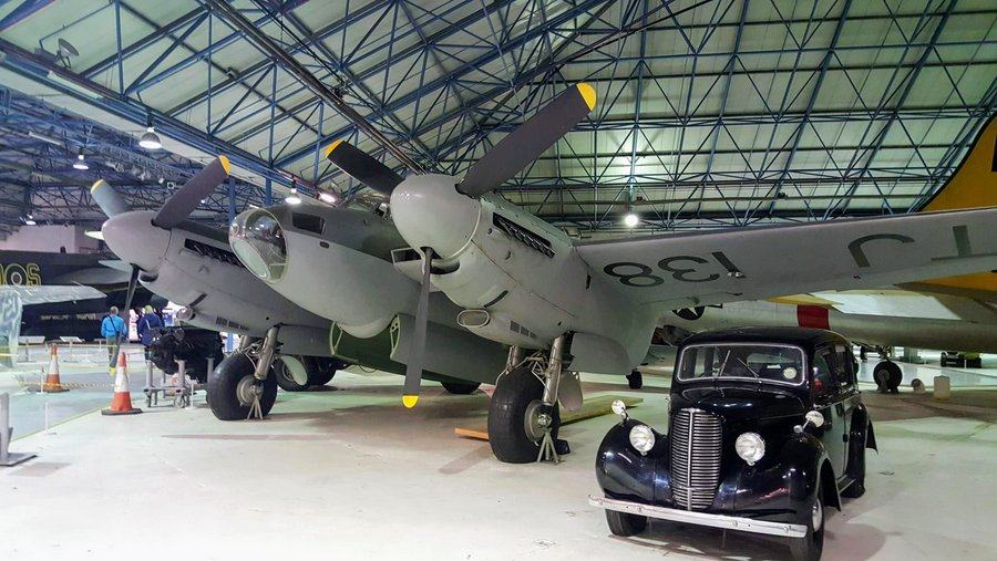 RAF Mosquito bomber with a black staff car parked under the wing.