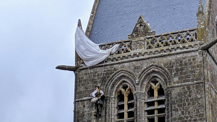 Close up of the dummy of a US paratrooper dangling from the church tower with his white parachute canopy caught up on the stone balustrade at the top