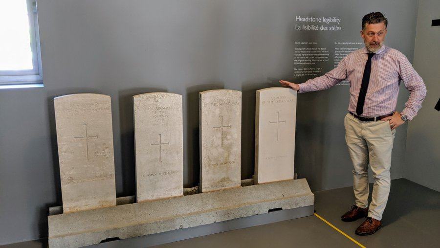 A man (Gareth Hardware) stands by a set of four headstones explaining their legibility characteristics