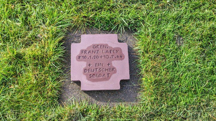 A redstone plaque in the grass naming a soldier and unknown soldier