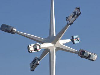 Six classic Porsche cars on spikes against a blue sky