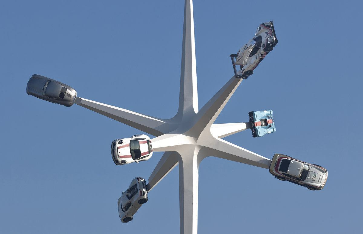 Six classic Porsche cars on spikes against a blue sky
