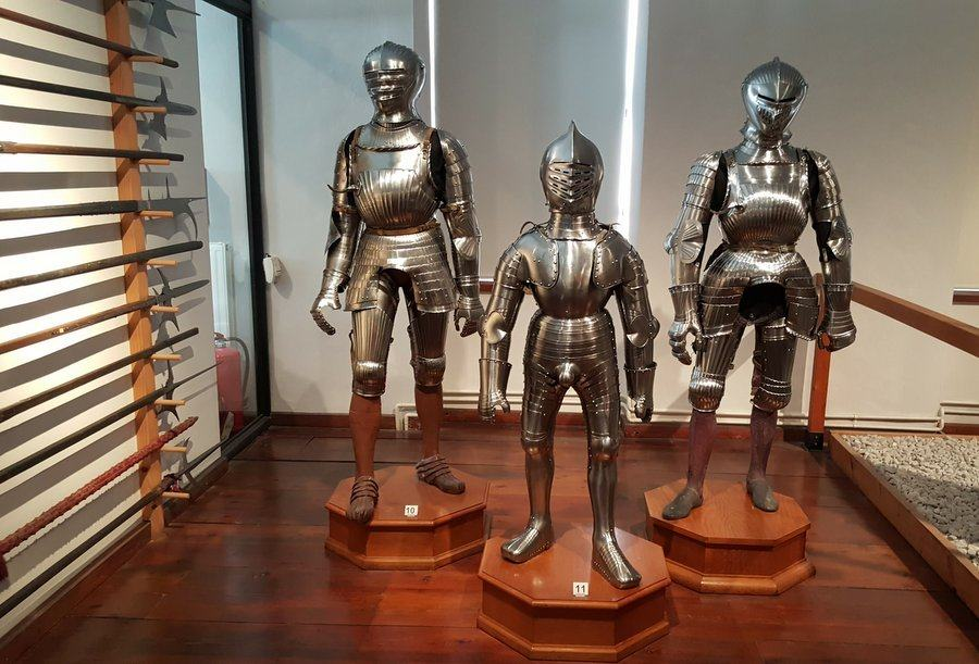 Three shiny suits of medieval armour on plinths