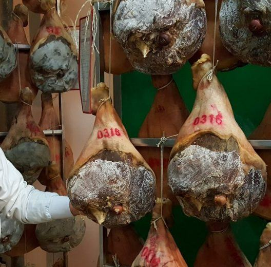 Manager stand with dried hams in storage racks