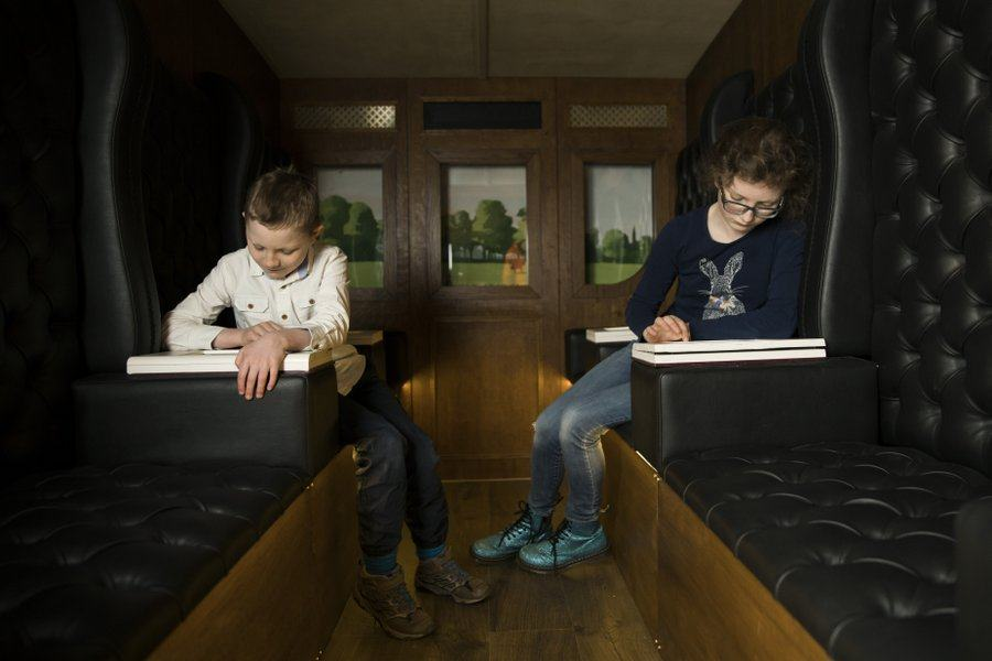 Children concentrating on drawing a circle in the swaying carriages at being Brunel museum in Bristol