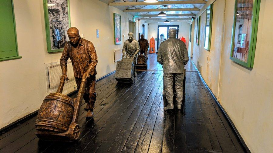 Statues of munitions workers pushing sack trucks with gunpowder barrels in the corridor