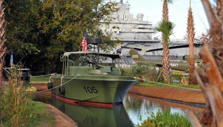 A small green Vietnam War era patrol boat alongside a small dock